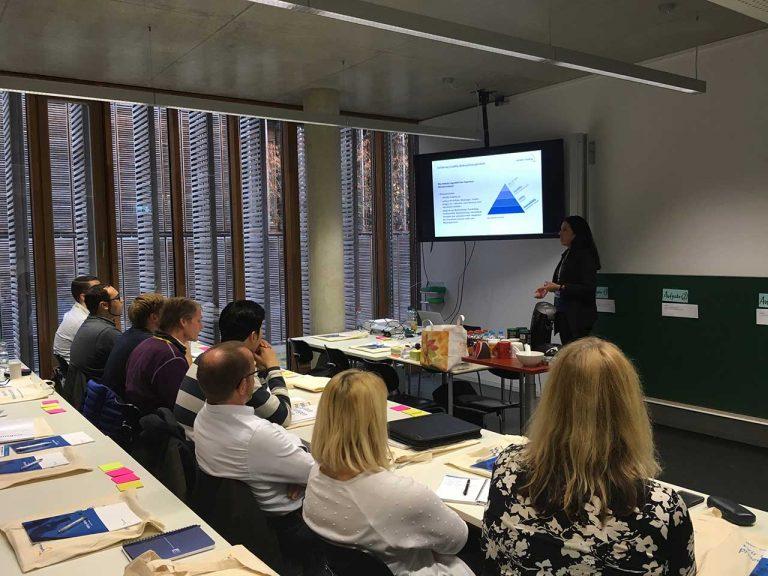 Usability Workshop im Buren - Frau Linda Alers steht an einem Bildschirm und erklärt etwas