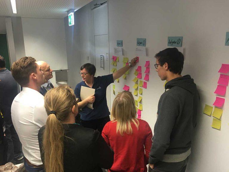 Teilnehmer des Uability Workshops von rocket-media arbeiten an einer Wand mit Post-Its - Frau Carmen Hartmann-Menzel erklärt etwas