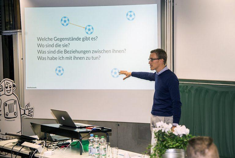 Moritz Tuerck steht vor einer Leindwand in einem Hörsaal und spricht zu den Zuhörern
